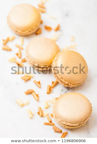 Golden luxury dessert cake macaron or macaroon with gold on marble kitchen table background. Top vie Stock photo © DenisMArt