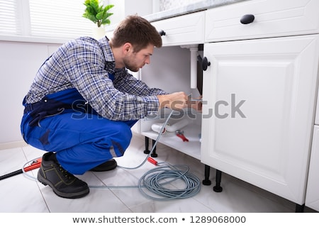 Male Plumber Cleaning Clogged Sink Pipe With Drained Cable Stock photo © AndreyPopov