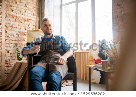 Elégedett művész munkaruha üveg vörösbor élvezi Stock fotó © pressmaster