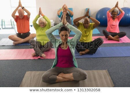 front view of senior people doing yoga with female trainer in fitness studio stock photo © wavebreak_media