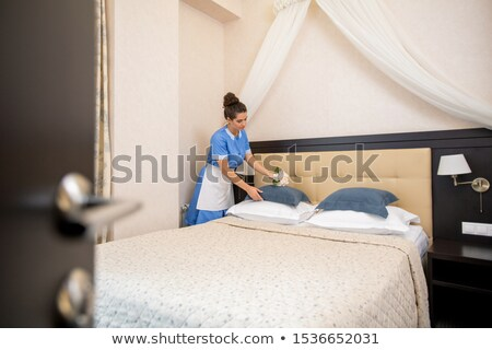 Young chamber maid in uniform putting flowers on one of pillows while making bed Stock photo © pressmaster