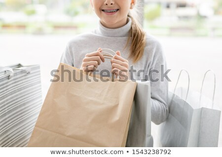 Smiling girl in white pullover holding paperbags while sitting in trade center Stock photo © pressmaster