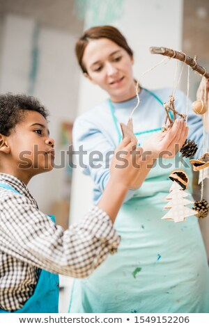 Serious schoolchild looking at one of handmade Christmas toys and symbols Stock photo © pressmaster