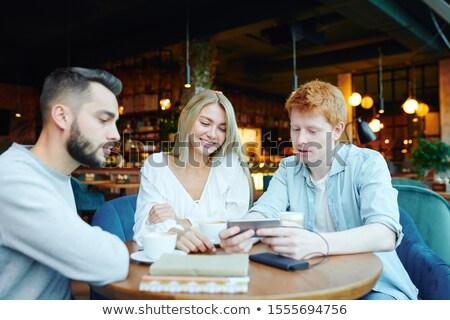 молодые друзей кофе смотрят любопытный видео Сток-фото © pressmaster