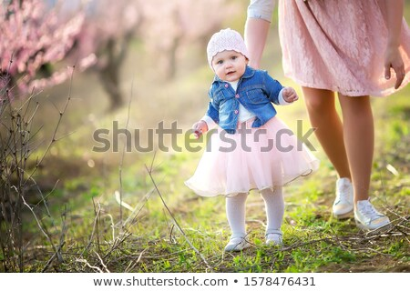 Mom with a child walk outdoors among the flowering spring trees and breathe fresh air Stock photo © ElenaBatkova