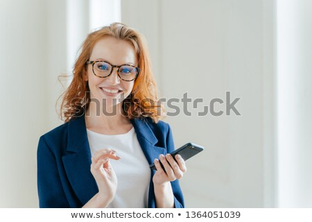 Elegant female copywriter with broad smile searches information for article and publication on cell  Stock photo © vkstudio
