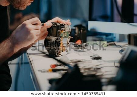 Foto stock: Woking Process Unknown Man Repairs Professional Digital Camera Uses Screwdriver Poses At Workplac