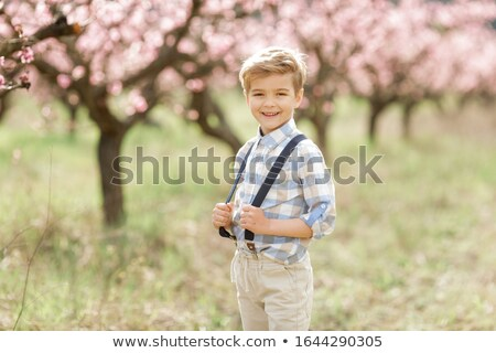 Boy dressed in a brace shirt and suspenders walks in the park Stock photo © ElenaBatkova