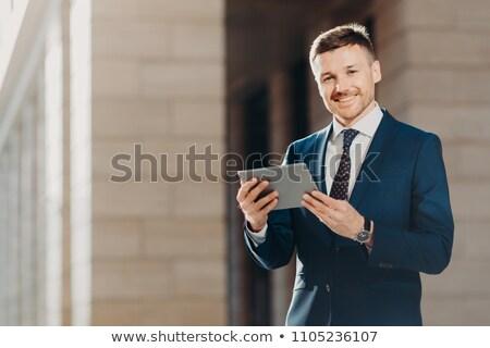 Happy male entrepreneur wears formal black suit, holds modern tablet computer, checks financial news Stock photo © vkstudio