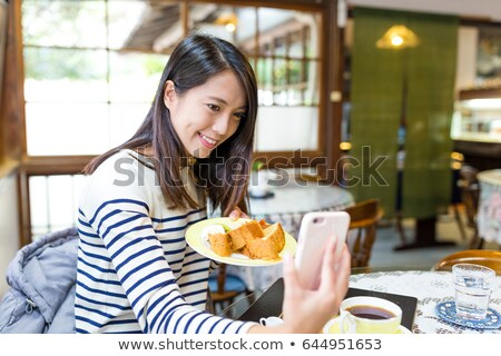 Smiling asian woman taking a photo of her pancakes Stock photo © deandrobot