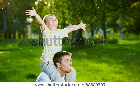 Cheerful small son on shoulders at the daddy in a summer Stock photo © Lopolo