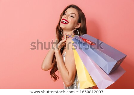 Cheerful woman in bright sequins dress holding shopping bags. Stock photo © deandrobot