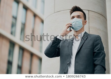 People in respiratory masks at blue city background, people call to prevent spreading covid-19 Stock photo © robuart