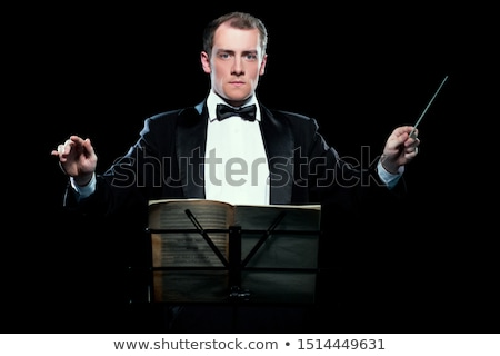 young orchestra conductor directing with his baton stock photo © feedough