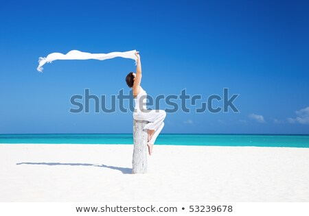 happy woman with white sarong on the beach stock photo © dolgachov