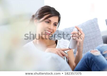 Bájos fiatal nő küldés üzenet mobiltelefon kék Stock fotó © pablocalvog