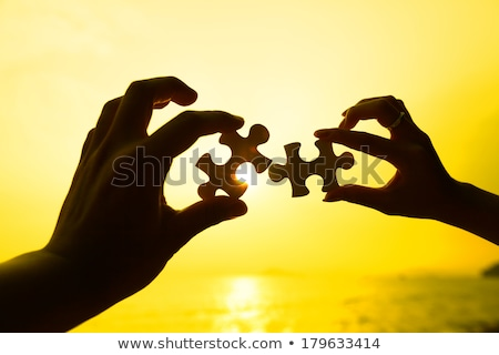 man trying to connect puzzle pieces stock photo © dolgachov