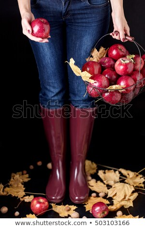 Woman wearing boots standing with a basket of fall leaves stock photo © sarahdoow