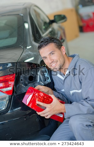 cheerful serviceman unscrewing wheel in car workshop stock photo © nejron