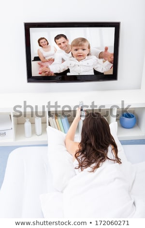Beautiful woman lying in bed watching television Stock photo © dash