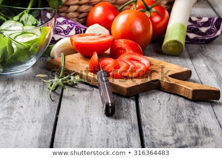 Vegetables on chopping board - focus on tomatoes Stock photo © elly_l