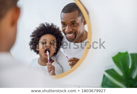 Young man teaching kids how to clean the teeth Stock photo © zurijeta