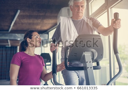 Man exercising on elliptical trainer. Stock photo © Kurhan
