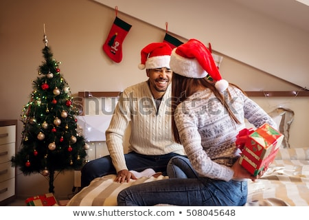 cheerful attractive young woman hiding a gift behind her back stock photo © deandrobot