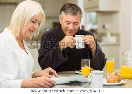 Woman in dressing gown having coffee for breakfast Stock photo © Kzenon