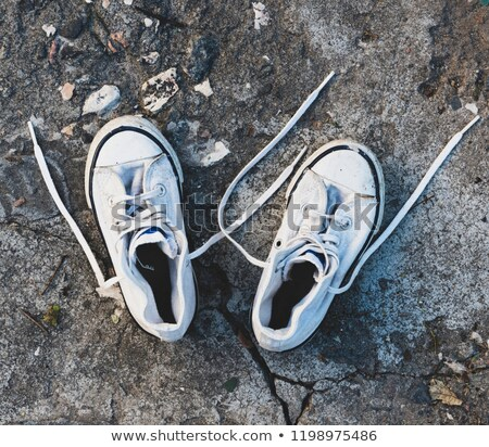 Top view of worn gray sneakers on white asphalt road Stock photo © stevanovicigor
