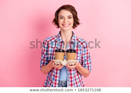 Two smiling attractive young women holding cups of takeaway coffee Stock photo © deandrobot
