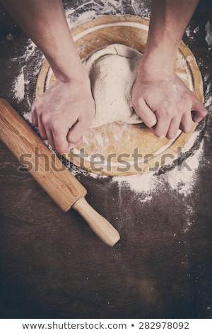 Man cooking dough for two pizzas on the wooden table stock photo © Karpenkovdenis