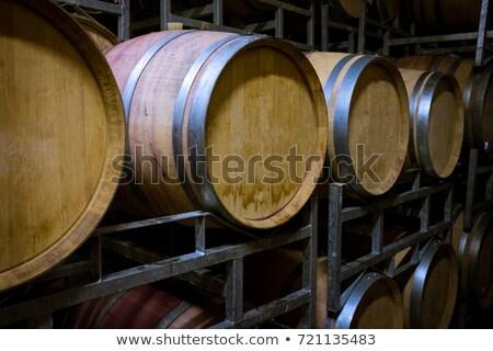Foto stock: Wine Barrels And Bottles Age Inside Cellar