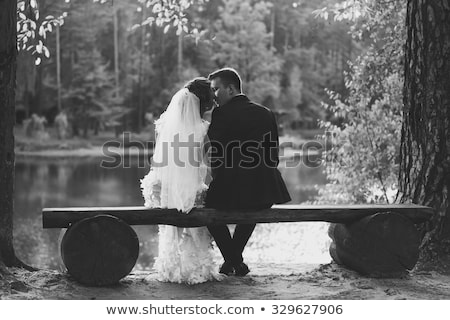 The bride and groom sit on a bench. The groom hugs the bride stock photo © d_duda