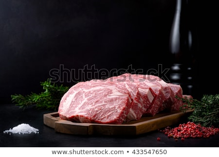 raw uncooked beef meat steaks on white wooden background stock photo © yelenayemchuk