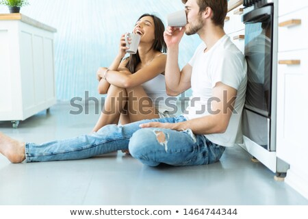 Stock photo: Handsome woman with cup of tea sitting on floor