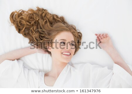 pretty blonde woman in bathrobe resting on bed stock photo © deandrobot