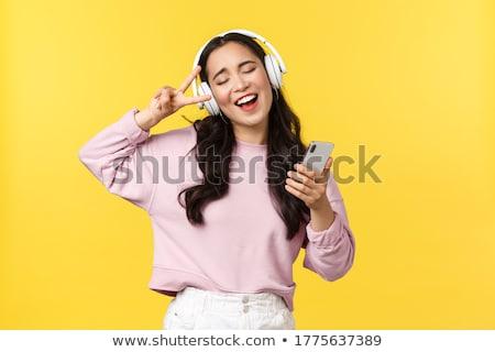 Boldog csinos ázsiai nő fejhallgató zenét hallgat Stock fotó © deandrobot