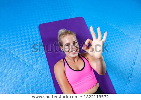 Smiling young sports lady showing okay gesture. Stock photo © deandrobot