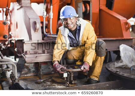worker turning wheel on oil rig stock photo © is2