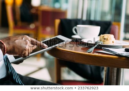 man using digital tablet while having cup of coffee stock photo © wavebreak_media