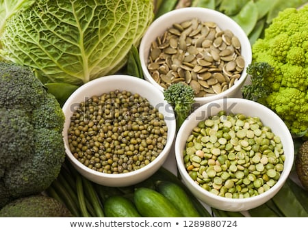 Bowl of mung beans and split peas and pumkin seeds with raw organic green toned vegetables. Stock photo © DenisMArt