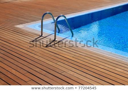 Foto stock: Blue Swimming Pool With Teak Wood Flooring