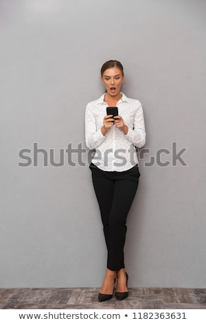 shocked business woman standing over grey wall background using mobile phone stock photo © deandrobot