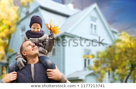 Stock photo: father and son with autumn maple leaves over house