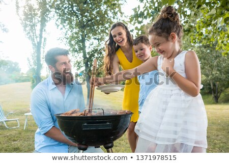 Сток-фото: Cute funny girl preparing meat on BBQ charcoal grill
