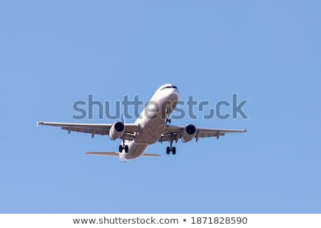 a white airplane flying in a clear pale blue sky stock photo © galitskaya