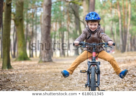 happy kid boy of 5 years having fun in the park with a bicycle on beautiful day stock photo © galitskaya