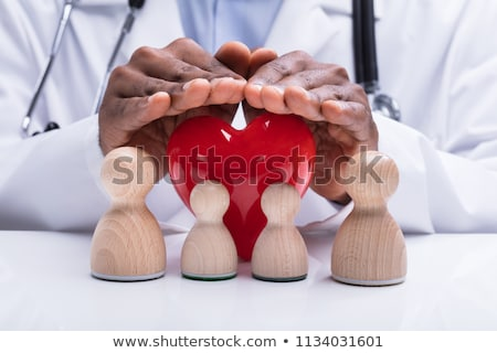 Doctor's Hand Protecting Wooden Pawn Family And Red Heart Stock photo © AndreyPopov