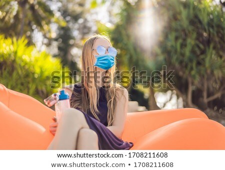 Summer lifestyle portrait of pretty girl in medical mask sitting on the orange inflatable sofa and d Stock photo © galitskaya